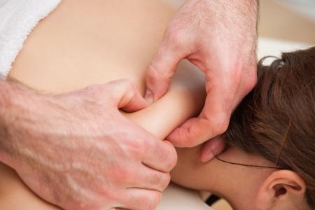 spinal manipulation: Retro della donna che viene spremuto da mani di medico in una stanza Archivio Fotografico