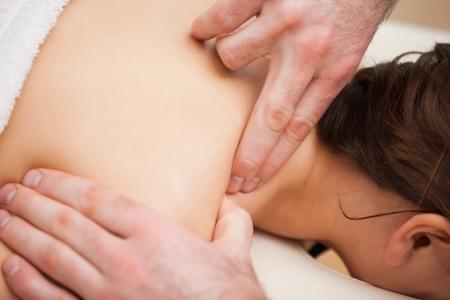 spinal manipulation: Dottore premendo la spalla del suo paziente in una stanza