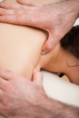 spinal conditions: Chiropractor massaging the shoulders of his patient while using his thumb indoors