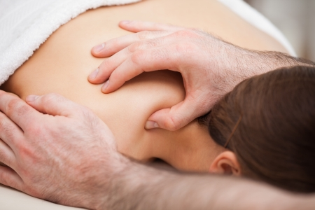 spinal conditions: Osteopath massaging his patient while pressing his tumb in a room