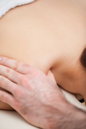 spinal conditions: Shoulder of a woman being massaged by a doctor in a room