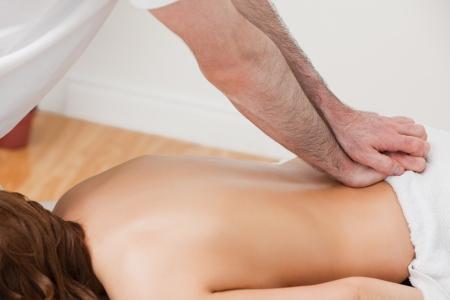 spinal manipulation: Terapeuta massaggiare la parte posteriore del suo paziente in piedi in una stanza