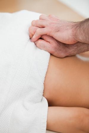spinal manipulation: Close-up del medico massaggiare la schiena del suo paziente in una stanza