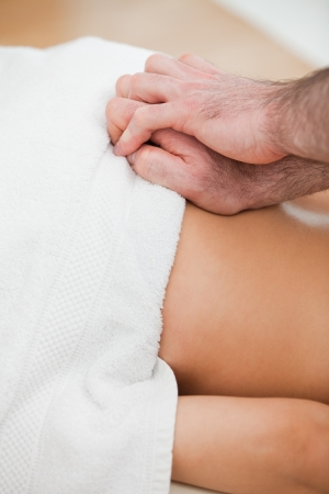 spinal conditions: Close-up of doctor massaging the back of his patient in a room