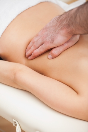 spinal conditions: Close-up of a therapist massaging a woman indoors