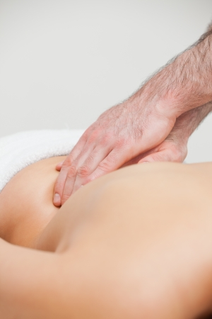 spinal manipulation: Close-up of an osteopath massaging the back of woman in a room