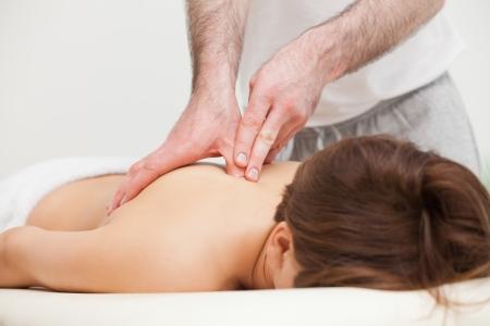 trapezius: Terapeuta de masaje de la parte superior de la espalda de una mujer mientras est� de pie en una habitaci�n Foto de archivo