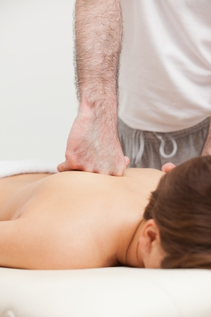 spinal conditions: Doctor massaging his patient while using the back of his hand in a room Stock Photo