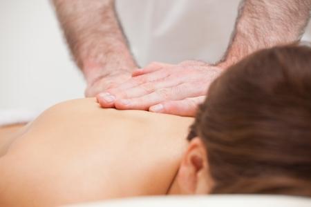 spinal manipulation: Close-up di un medico massaggiare la schiena di una donna in casa Archivio Fotografico