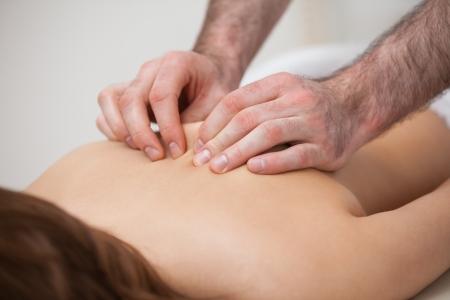 spinal manipulation: Chiropratico massaggiare il suo paziente mentre si utilizza la punta delle dita in una stanza