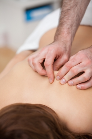 back sprains: Back of a woman being massaging while fingertips of doctor in a room Stock Photo