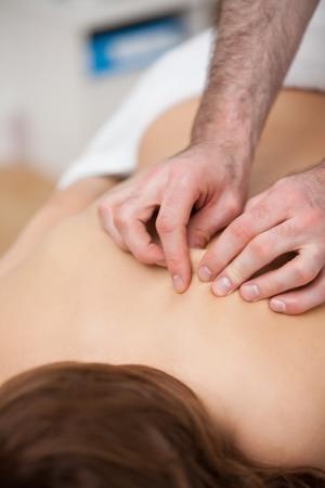 spinal manipulation: Indietro di una donna che viene portata di mano, mentre massaggio di medico in una stanza