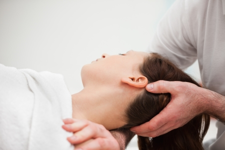 male massage: Doctor manipulating the neck of a woman in a room Stock Photo