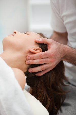 osteopath: Neck of a woman being manipulating by a therapist in a room Stock Photo