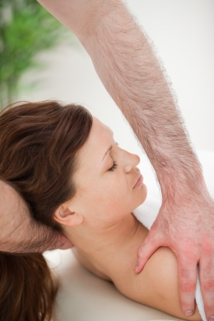 Therapist manipulating the neck of his patient while holding her shoulder indoors photo