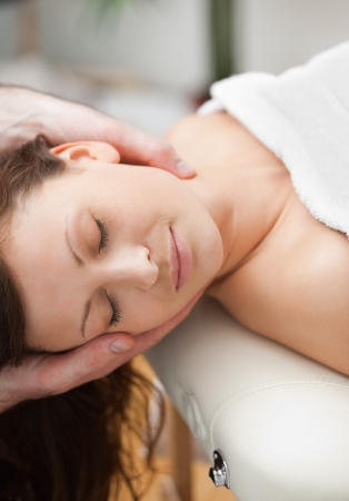 unwind: Peaceful woman being massaging on the neck by a therapist in a room