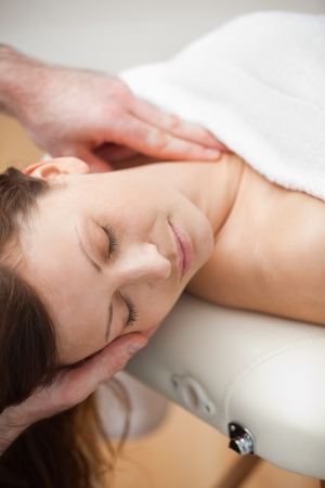 Neck of a patient being massaged by a chiropractor in a room photo