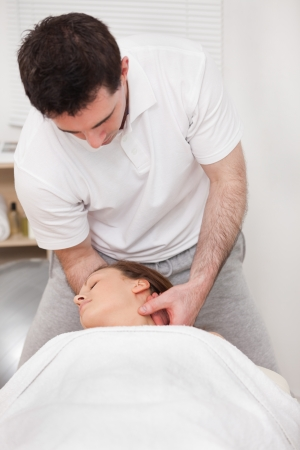 Therapist manipulating the neck of his patient while standing in a room photo