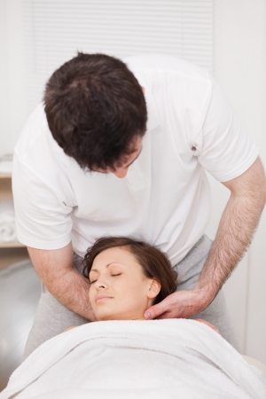 Therapist massaging the neck of a woman while holding her head in a room photo