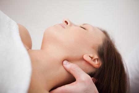 alineaci�n: Primer plano de la fisioterapeuta presionando su pulgar en el cuello de una mujer dentro Foto de archivo