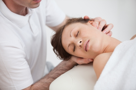 osteopata: Mujer que da masajes por el m�dico al tiempo que el giro de la cabeza en el lado inddor Foto de archivo