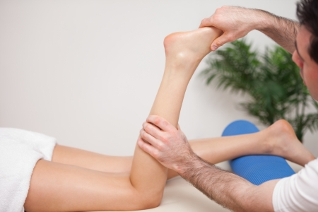 neuromuscular reeducation: Doctor manipulating the leg of his patient  in a room