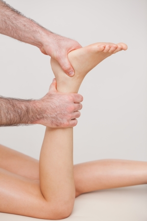 muscle retraining: Podiatrist manipulating the ankle of his patient in a room