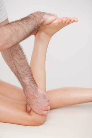 Podiatrist manipulating the leg of his patient while holding his foot and his knee indoors Stock Photo - 16204444