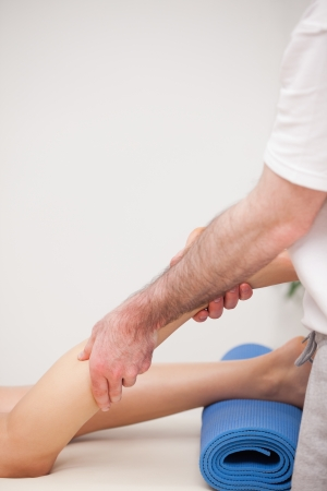 Podiatrist massaging the leg of his patient while standing in a room photo