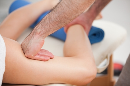 manipulating: Chiropractor manipulating the leg of his patient while holding his ankle and his thigh indoors