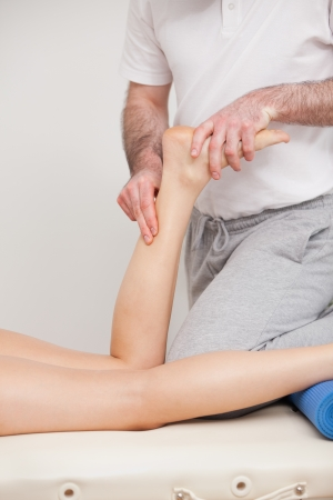 Podiatrist massaging the ankle of a woman in a room photo
