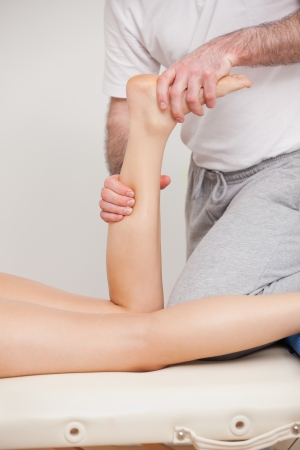 A doctor manipulating the ankle of his patient ina room Stock Photo - 16206788