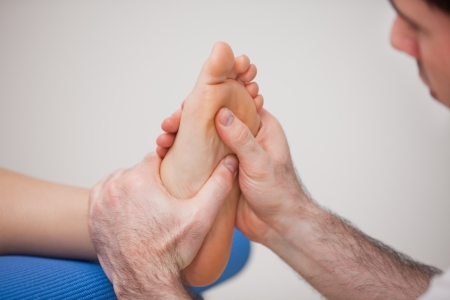 neuromuscular reeducation: Podiatrist practicing reflexology on the foot of woman in a room