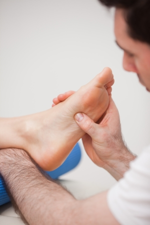 Reflexologist massaging the foot of his patient in a room photo