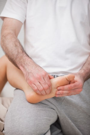 reflexologist: Reflexologist manipulating the sole of the patient in a room