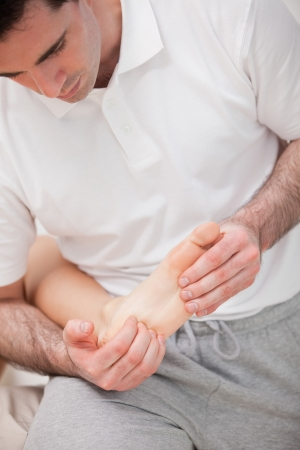 reflexologist: Reflexologist massaging the sole of the patient in a room