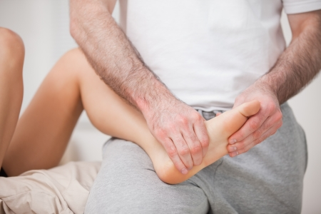 reflexologist: Reflexologist manipulating the foot of his patient while holding it on his thigh indoors