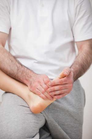 neuromuscular reeducation: Podiatrist manipulating the foot of a woman while holding it on his thigh indoors