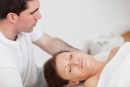 Masseur massaging the neck of his patient  in a room photo