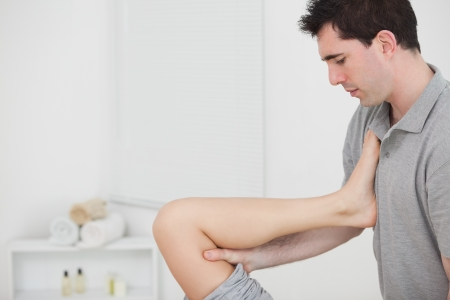lower limb: Chiropractor raising the leg of his patient against his chest in a room