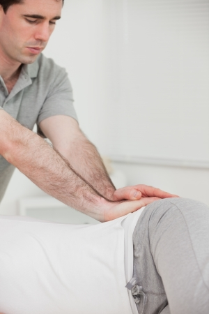 Serious chiropractor pressing the hip of his patient in a room photo