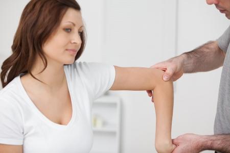 Arzt untersucht den Arm seines Patienten in einem Raum