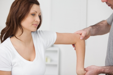 muscle retraining: Doctor examining the arm of his patient in a room Stock Photo
