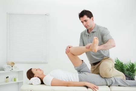 Chiropractor stretching the leg of his patient while holding it in a medical room photo