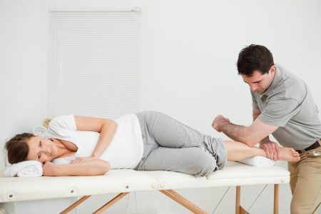 Doctor manipulating the leg of his patient while using his elbow in a room Stock Photo - 16204561