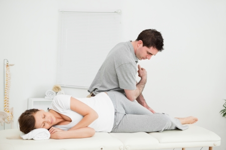Chiropractor massaging the thigh of his patient while using his elbow in a room photo