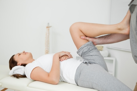 muscle retraining: Woman putting her foot on the chest of her doctor while stretching her leg indoors
