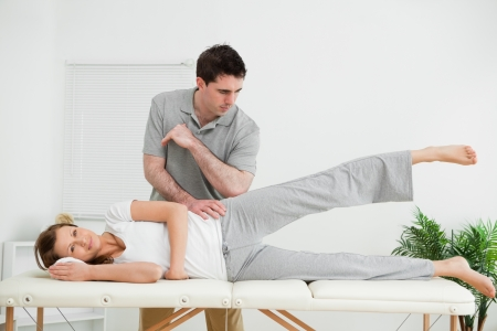 manipulating: Doctor pressing his elbow on her hip while woman raising her leg in a room Stock Photo