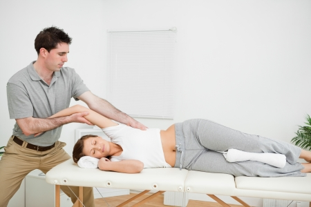 spinal conditions: Chiropractor stretching the arm of his patient while holding it in a room Stock Photo