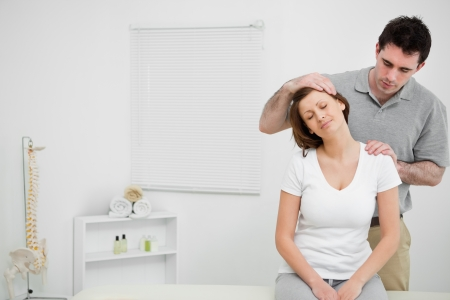 Doctor examining the neck of his patient while stretching it in a room photo